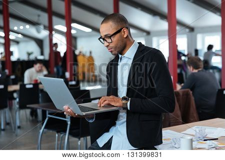 Serious smart businessman is standing and using laptop at the office