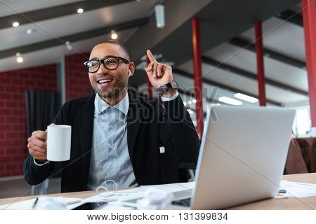 Casual businessman sitting with laptop and have an idea in the office