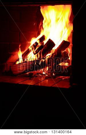 Interior background with fireplace. Firewood burning in fireplace