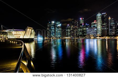 lluminated houses night city and water. City with lights reflected in the water. City lights reflected in the water. Night skyscrapers is reflected in calm water on a background of the night sky