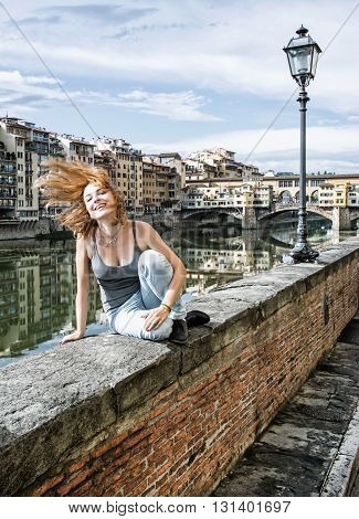 Young joyful caucasian woman tossing her hair on the wall in front of the Ponte Vecchio in Florence Tuscany Italy. Travelling theme. Arno river. Beauty and fashion. Historical buildings.
