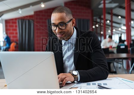 Young businessman working and typing on laptop in the office