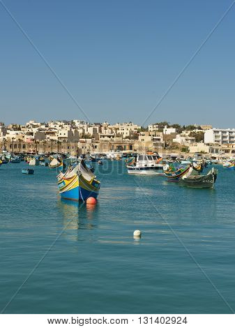 Traditional Maltese fishing boats with reflection in colourful maltese village Marsaxlokk in May 23,2016, MALTA.