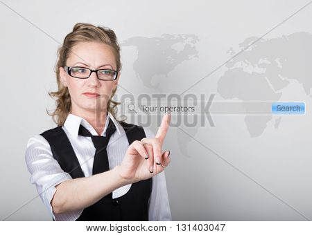 tour operators written in search bar on virtual screen. technology, internet and networking concept. Internet technologies in business and home. woman in business suit and tie, presses a finger on a virtual screen.