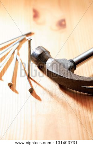Nails set near hammer on nice wooden background