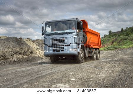 Poltava Region Ukraine - June 26 2010: Dump truck driving along the iron ore opencast road