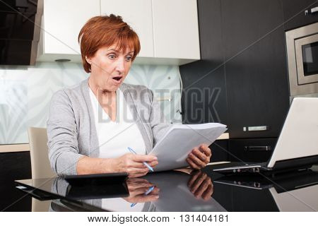 Woman sorting through her old receipts at home. Sad surprised businesswoman with document