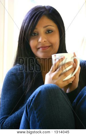 Young Attractive Asian Female With Cup Of Hot Drink
