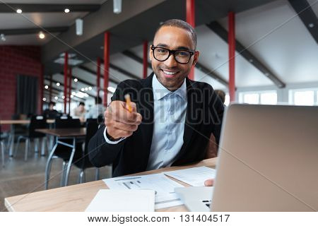 Businessman smiling and pointing with pncil at the working place