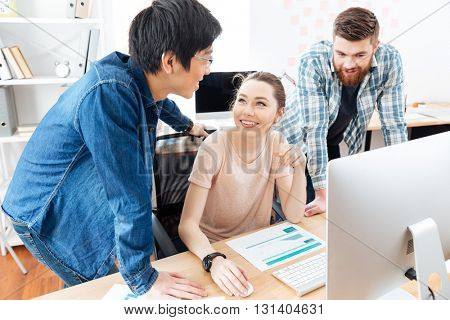 Three cheerful young businesspeople working in office together