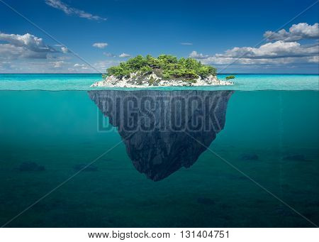 Idyllic underwater view of lone small island above and below the water surface in turquoise waters of tropical ocean.