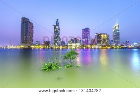 Ho Chi Minh City, Vietnam - March 29, 2016: Saigon at night with skyscrapers lights river sunset just off, shimmering cork adorn tree foreground growth prosperity country in Ho Chi Minh city, Vietnam