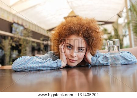 Attractive curly young woman with glass of water sitting and relaxing in cafe