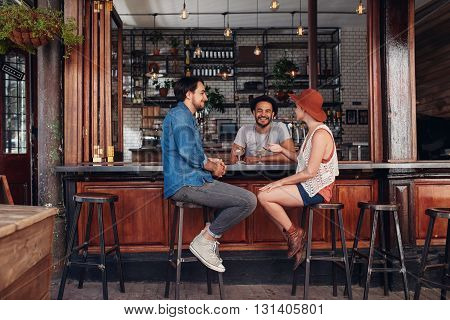 Group of young people sitting in a cafe and talking. Young men and women meeting at cafe table.