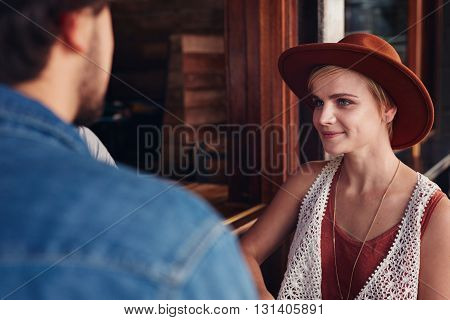 Portrait of beautiful young woman sitting at a cafe with her friend.