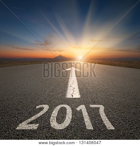 Driving on an empty road towards the setting sun and sunbeams to upcoming new 2017 year. Concept for success and passing time.