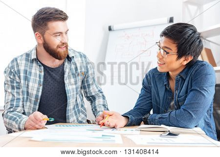 Two happy young businessmen talking and working together in office