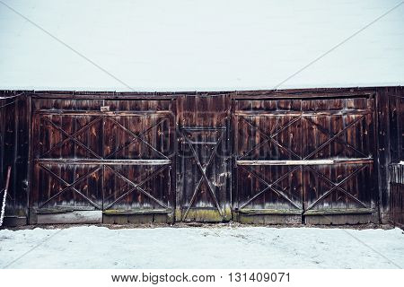 Old wooden barn covered with snow in Poland