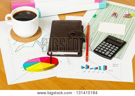 Cup of coffee, calculator, notebook and other stationery to the desktop background.