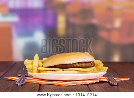 Hamburger, french fries, cutlery, napkin against the background of the hall cafe.