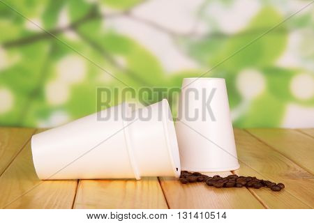 Disposable paper cups and coffee beans on a abstract green background.
