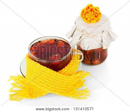 Bank and a cup of tea from rose hip berries isolated on white background.