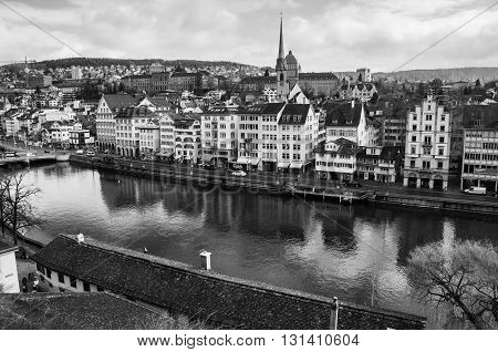 ZURICH, SWITZERLAND - FEBRUARY 27, 2014: Aerial view of old buildings in the city center of with Limmat river. Popular restaurants, cafes and shops. Car traffic and cloudy sky. Black and white
