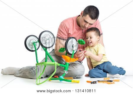 father and kid son fixing children bicycle together