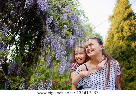 Woman and daughter walk in the garden.They are enthusiastically looking at the blooming wisteria.The faces of the enthusiastic smiles. They were good together.Best of the rest is walk in the fresh air