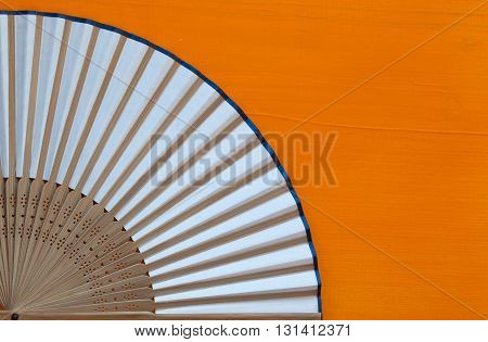 Typical Japanese hand fan made on the wooden orange table
