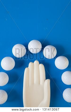 Detail of ceramic hand with golf balls on the blue wooden desk - Flat Lay Photography