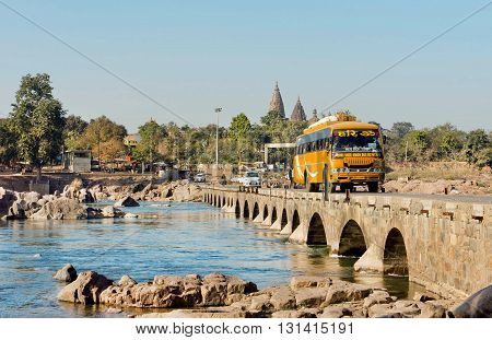 MADHYA PRADESH, INDIA - DEC 23, 2015: Yellow touristic bus driving through the narrow stone bridge on fast river on December 23, 2015 in Orchha. Madhya Pradesh is the 2nd largest indian state by area.