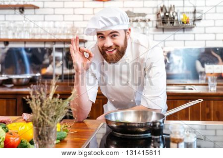 Cheerful bearded chef cook cooking and showing ok sign on the kitchen