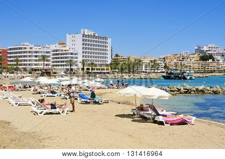 IBIZA, SPAIN - JUNE 19: Sunbathers in the popular Ses Figueretes Beach on June 19, 2015, in Ibiza Town, Spain. Ibiza is a well-known summer tourist destination in Europe