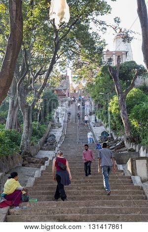 Kathmandu, Nepal - October 20, 2014: People climbing up the steep stairs to the buddhist temple Swayambunath.