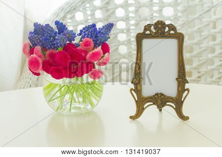 bunch of Muscari and Daisy Flowers on white table and vintage frame with copy space
