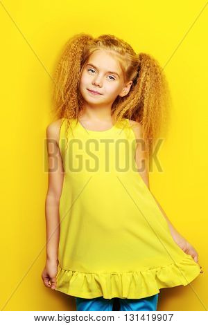 Joyful little girl with beautiful blonde hair over yellow background. Kid's style. Hairstyle.