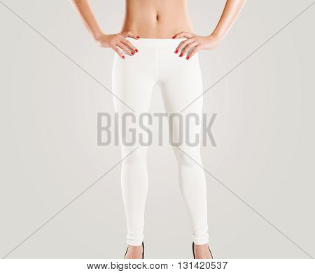 Woman wear blank white leggings mockup isolated on grey. Women in clear leggins template. Cloth pants design presentation. Sport pantaloons stretch tights model wearing. Slim legs figure in apparel.