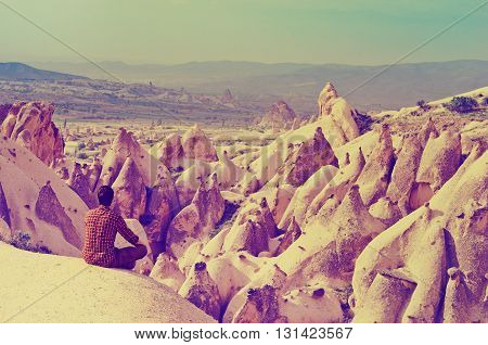 Traveler against the background of incredible mountains landscape with geological structures in Goreme Cappadocia Central Anatolia Turkey