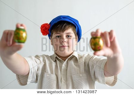 a boy in Russian national cap with cloves holding easter eggs