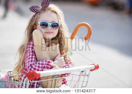 Little girl,with thick blonde long hair,dressed in a plaid shirt and denim shorts,on his head a black-and-red bow,wears sun glasses in blue frame,sitting in the shopping cart on wheels near a large supermarket