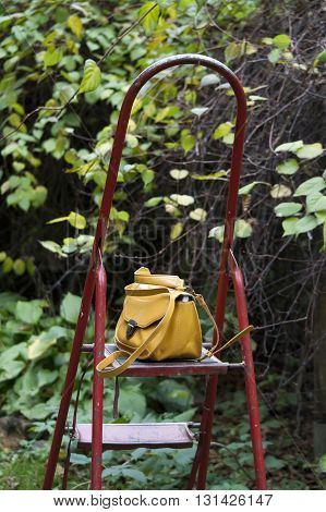 front view of yellow hippster handbag on red ladder in the garden