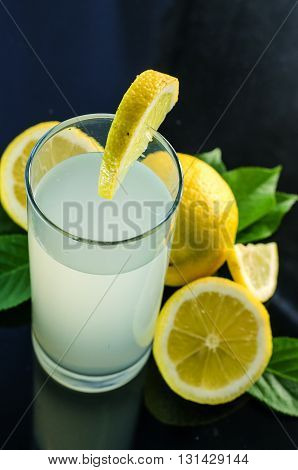 fresh lemon juice and lemon on a dark background