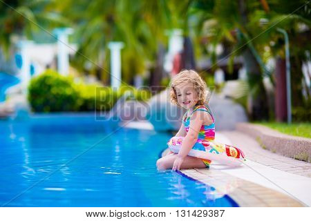 Little girl playing in outdoor swimming pool in tropical resort. Child learning to swim. Toddler kid with inflatable toy ring. Summer beach vacation for family with children. Water fun for kids.