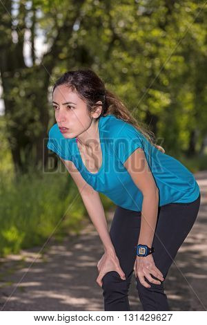 Woman concentrated looking before jogging in nature.