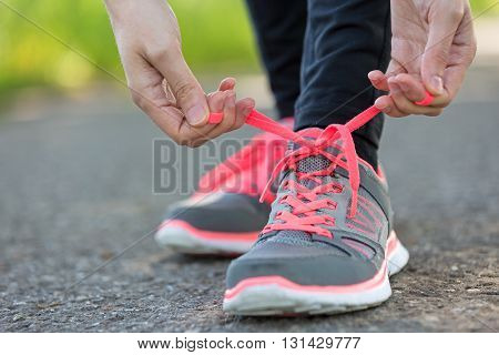Woman binding her shoes before a run in the nature. Close up of hands.