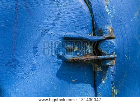 Old blue rusty door hinge in sunlight