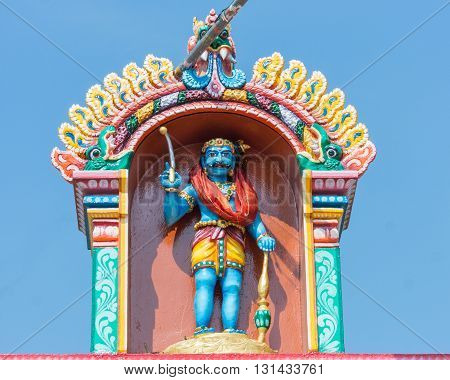 Chettinad India - October 16 2013: Ayyanar in a niche at his shrine above entrance gate in Pilivalam village. Blue sky.