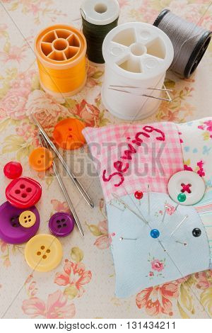 Sewing needles threads and buttons with a pin cushion