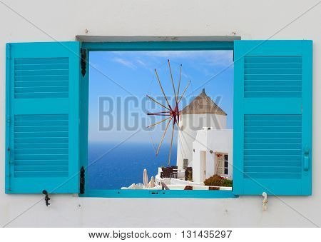 window with windmill of Oia at sunny day close up, Santorini